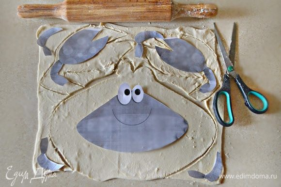 Слоеное дрожжевое тесто разморозьте при комнатной температуре. Немного раскатайте, посыпав поверхность мукой, и вырежьте с помощью шаблона крабика (по 2 шт каждой его составляющей).