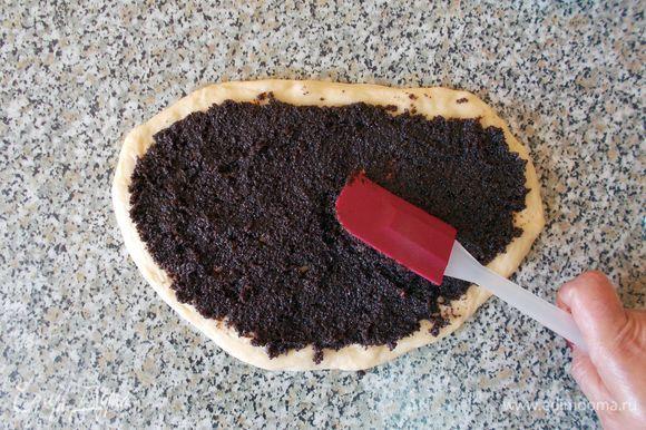 С помощью силиконовой лопатки (или ножа, ложки) равномерно размазываем начинку по тесту. Сворачиваем рулет, плотно прижимая тесто.