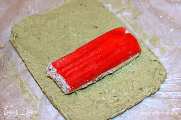 На застывшую массу из авокадо выкладываем застывшую фаршированную крабовую палочку.