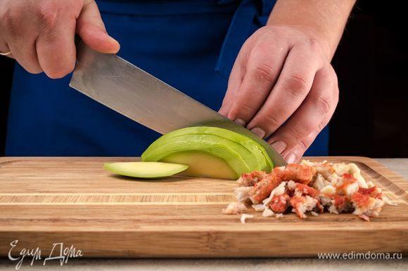 Авокадо очистите и нарежьте полосками, мясо краба нарежьте небольшими кусочками.