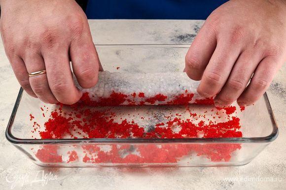 Освободите ролл от циновки, обваляйте его в икре летучей рыбы и нарежьте на порции.