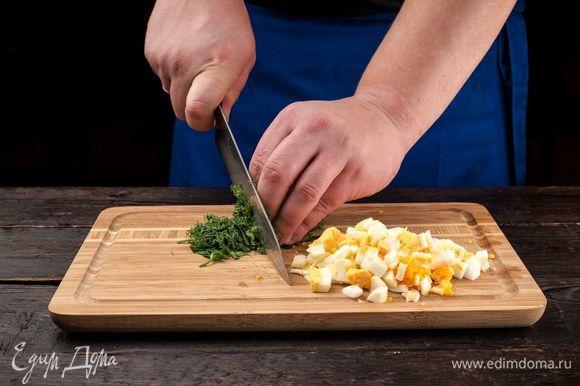 Отварите 3 яйца и нарежьте кубиками. Измельчите зелень.