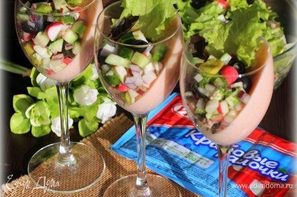 Вынуть бокалы с застывшим соусом из холодильника, положить в них крабовый салат и подать к столу.