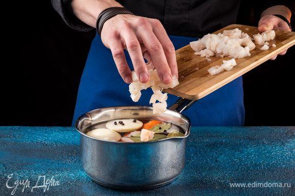 Положите рыбу в кастрюлю, добавьте очищенную морковь, лук, специи. Варите в течение 15 минут.