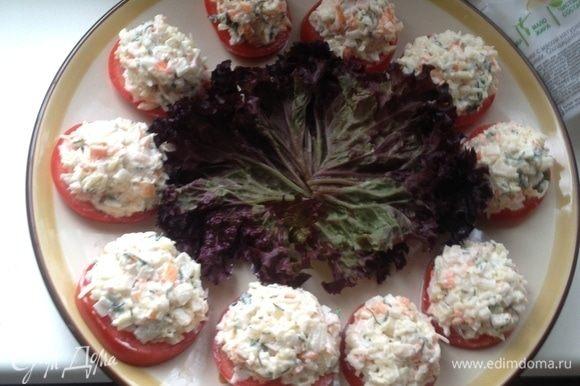 Помидоры выложить на блюдо и по столовой ложке салата. Красиво оформить зеленью как вам нравится.