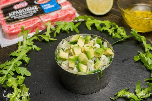 Выкладываем салат в порционную тарелку или форму, а сверху кладем нарезанное кубиками авокадо.