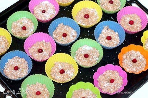 Формируем печенье. Можно выложить на противень, застеленный пергаментной бумагой. Или как у меня, выложить по 1 столовой ложке в силиконовые формочки. Посыпать заготовки кокосовой стружкой и украсить ягодами.