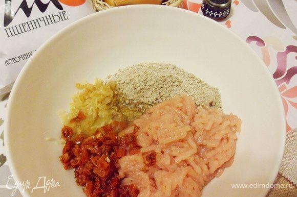 Отделить белки от желтков. К куриному фаршу добавить пропаренный чеснок и лук, перемолотые пшеничные отруби, яичные белки и нарезанные вяленые помидоры.