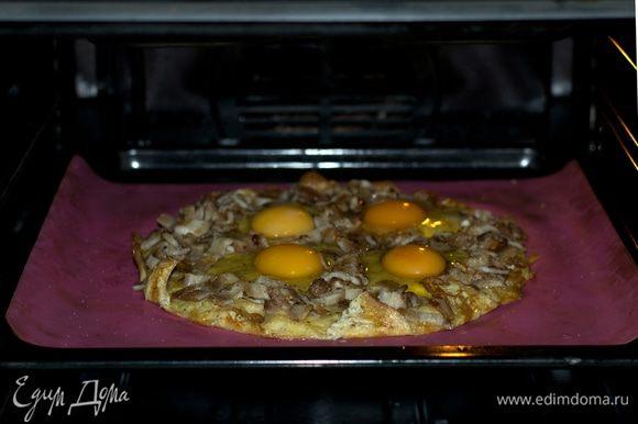 Выложить бекон на запеченную основу. Аккуратно добавить 4 яйца. Запекать 12 минут при 200°С.
