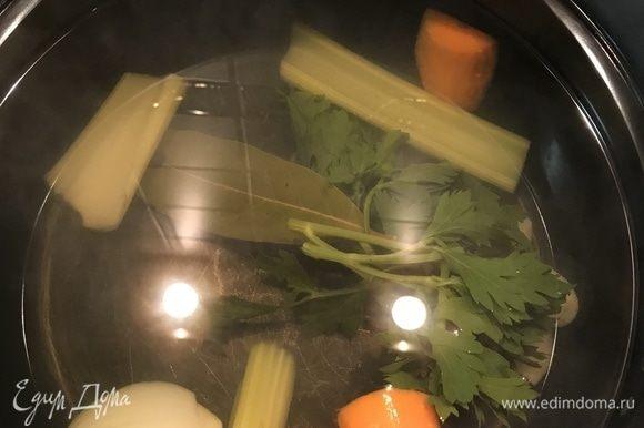 Сначала приготовим овощной бульон. В кастрюлю наливаем 1,5 л воды. И ставим на огонь. Тем временем очищаем 1 морковь и режем произвольно. Стебель сельдерея также режем крупно. Добавляем все в закипающую воду вместе с одной луковицей и зеленью сельдерея. Солим по вкусу и не забываем про перец горошком. Оставляем вариться.