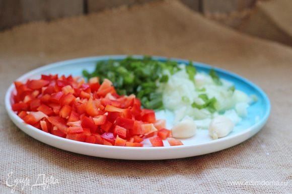 Бекон, перцы, сельдерей, лук и обесшкуренные помидоры нарезать кубиками, чеснок пропустить через давилку. В большой кастрюле, желательно с толстым дном, разогреть масло и положить бекон. Выжарить его на среднем огне до золотистого цвета. Положить в кастрюлю перец, лук и сельдерей, после чего обжаривать 3–5 минут до прозрачности лука. Добавить чеснок и обжарить все еще минуту.