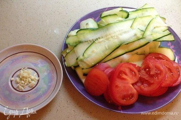 Подготовить ингредиенты. Чеснок мелко порубить, цукини нарезать тонкими пластинами, помидоры — кружками.