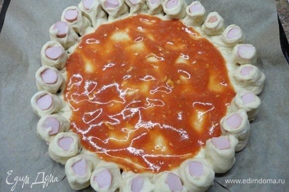 Бортики разрежьте по размеру сосисок и выверните срезом вверх. Середину смажьте томатным соусом, смешанным с горчицей.