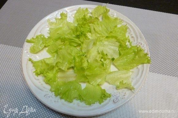 На сервировочной тарелке собираем салат. Листья салата порвем крупными кусками и разложим на тарелке.