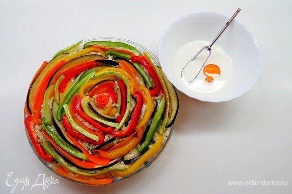 Сливки взбить с яйцом и с помощью ложечки влить смесь между всех овощей.