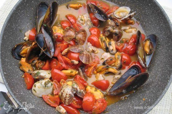 Соус, где готовились морепродукты, уварить примерно до полстакана, процедить через несколько слоев марли. Соус вернуть в сковороду, выложить готовые помидоры, морепродукты, прогреть.