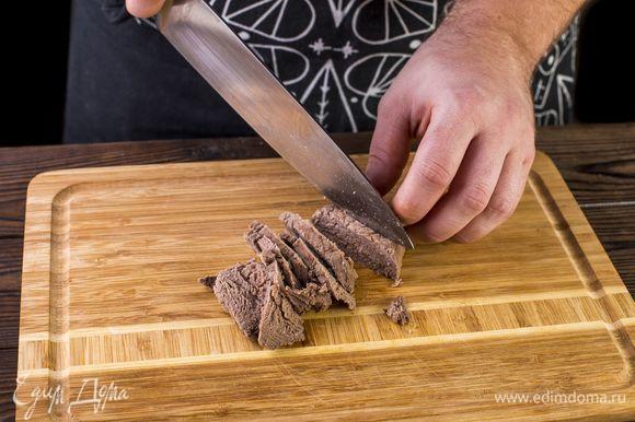 Готовое мясо выньте из бульона, остудите и нарежьте кусочками.