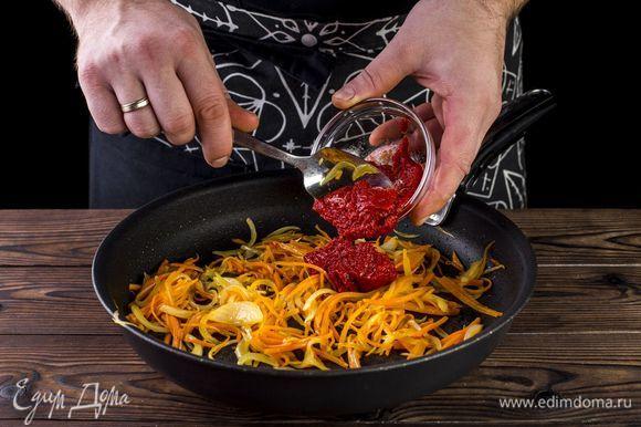 Лук и морковь тушите на оливковом масле до золотистого цвета, добавьте томатную пасту. Все хорошо перемешайте.