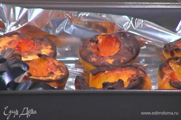 Персики разрезать пополам и, удалив косточки, выложить срезами вверх в небольшой противень, выстеленный пищевой фольгой, а затем запечь под разогретым грилем до загорелой корочки.