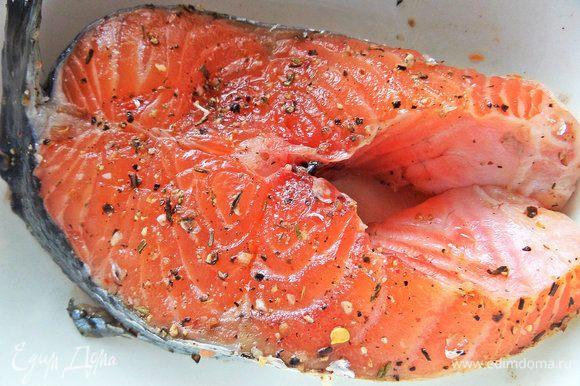 Обсыпать заранее большой лососевый стейк лимонным перцем, солью и ароматными травами. Накрыть и убрать в холодильник.
