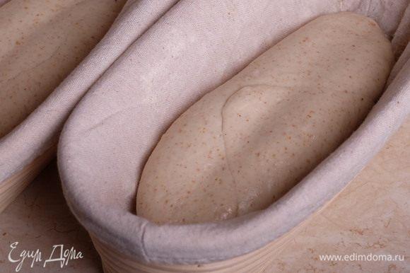 Тонкой деревянной скалкой, подпыленной мукой, продавить вмятину вдоль заготовки, поместить в расстоечную корзинку швом вверх (не вмятиной!) и поставить на расстойку на 2 часа. За это время заготовки должны увеличиться в объеме.