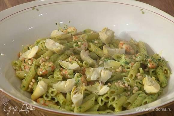 Макароны с креветками выложить в блюдо, посыпать оставшимися кедровыми орехами и украсить артишоками.
