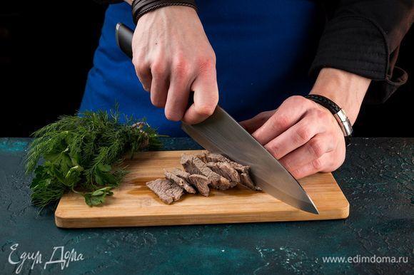 Нарежьте отварное мясо соломкой.