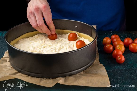 Слегка утопите в ней томаты черри целиком на расстоянии 2–3 см друг от друга.