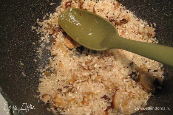Всыпать рис (у меня сорт арборио), рис не промывать. Помешивая готовить 2 минуты. Влить сухое белое вино, дать алкоголю выпариться. Теперь влить два половника бульона, перемешать. Ризотто необходимо во время приготовления постоянно помешивать, рис готовится около 16 минут, подливать по половнику горячий бульон по мере его впитывания.