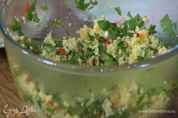 Приготовить салат: готовый теплый кускус перемешать со сливочным и оливковым маслом, затем добавить чили, измельченную зелень, посолить, поперчить и еще раз все перемешать.
