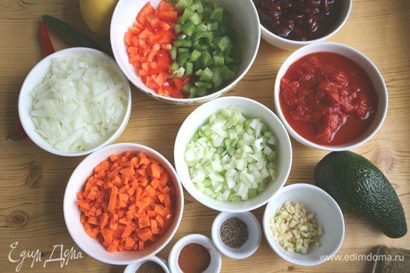 Морковь, лук почистить. Болгарский перец порезать на половинки, освободить от плодоножек и семенной части. Порезать на мелкие кубики морковь, лук, болгарский перец, стебли сельдерея. Порезать мелко чеснок.