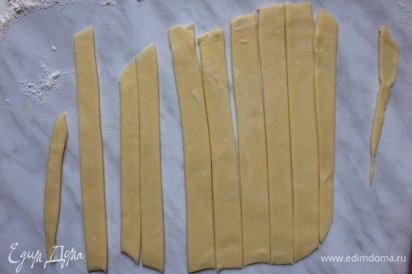 Достаньте из холодильника второй диск теста, выложите на рабочую поверхность и раскатайте в тонкий пласт. При помощи ножа или фигурного резака нарежьте тесто на полоски.