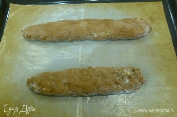 Разделить тесто на 2 части, скатать 2 колбаски диаметром 3–4 см. Выложить на застеленный пергаментом противень (или антипригарный коврик). Немного сплющить, чтобы печенье в итоге получилось овальной формы. Поставить в духовку на 25–30 минут.