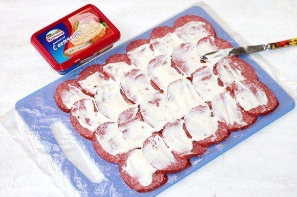 Смазываем верх кружочков колбасы мягким сыром Hochland.