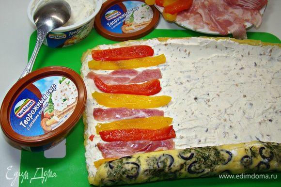 Остывший рулет развернуть и промазать сливочным сыром (у меня со вкусом лесным грибов). На сырную начинку уложить нарезанные запеченные перцы и подкопченные ломтики бекона.