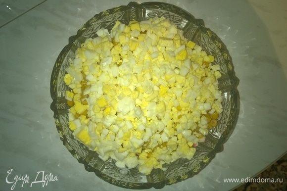 Высыпаем порезанные куриные яйца в готовую вазу для салата.