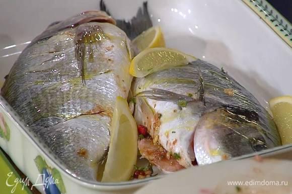 На коже рыбы сделать неглубокие поперечные надрезы, выложить ее в жаропрочную керамическую посуду и наполнить брюшки ореховой начинкой, затем слегка сбрызнуть дораду оливковым маслом, сверху и вокруг разложить дольки лимона, посолить и поперчить.
