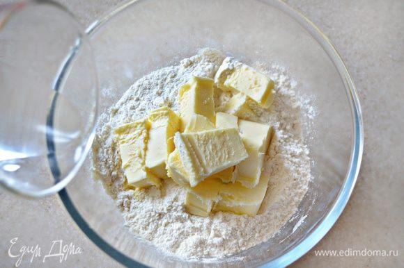 К муке добавьте рубленое масло, щепотку соли и 2 ст. л. холодной воды, замесите тесто.