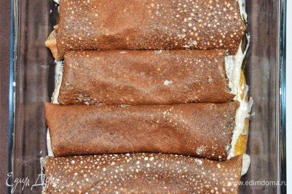 Последний шаг — запекаем нафарширанные начинкой блины под соусом. Разогрейте духовку до 190°С. Каждый блин намажьте тонким слоем баклажанной начинки и сверните, подогнув бока внутрь, чтобы начинка не вытекла при запекании. В блюдо для запекания налейте немного растительного масла, а затем соус бешамель тонким слоем. Выложите нафаршированные блины в один ряд и обильно залейте соусом бешамель, включая бока. Сверху, при желании, посыпьте сыром. Закройте блюдо фольгой и отправьте в духовку на 15 минут. Затем уберите фольгу и запекайте еще 5 минут. Блюдо готово.