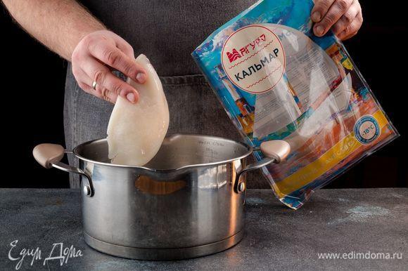 Тушки кальмаров ТМ «Магуро» разморозьте и промойте. Налейте в кастрюлю воды, посолите, добавьте перец горошком и лавровый лист. Доведите до кипения и поочередно окунайте каждую тушку кальмара на 10 секунд в кипящую воду. Готовые кальмары обсушите.