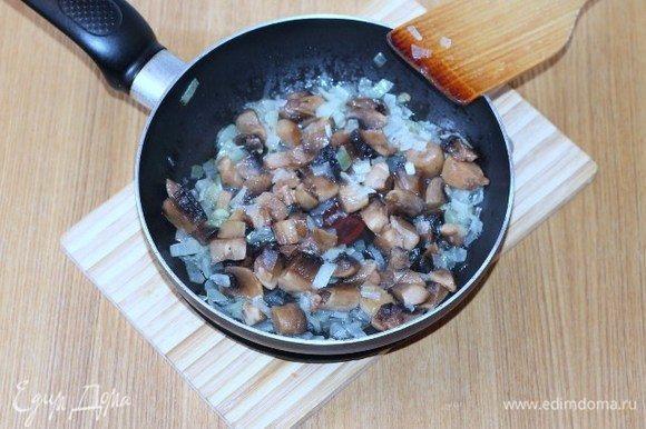 Добавляем порезанные дольками шампиньоны, сливочное масло, солим, перчим и жарим до готовности грибов.