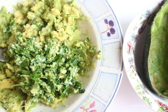 Приготовить песто из зелени. Зелень мелко нарезать, чеснок почистить, выдавить через пресс. В ступку поместить зелень, кедровые орехи, чеснок, соль, перец, оливковое масло. Растолочь. Добавить к авокадо. Перемешать.