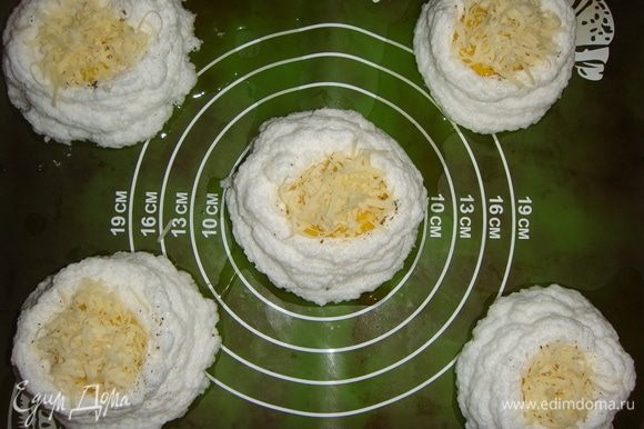 Посыпать натертым сыром и поставить в разогретую до 150°С духовку на 15–20 минут.