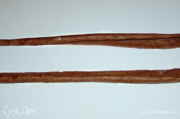 Из светло-коричневых кусочков теста раскатать длинные полоски (длина должна быть равна длине формы, в которой будет выпекаться хлеб) и свернуть каждую по всей длине в рулетик.