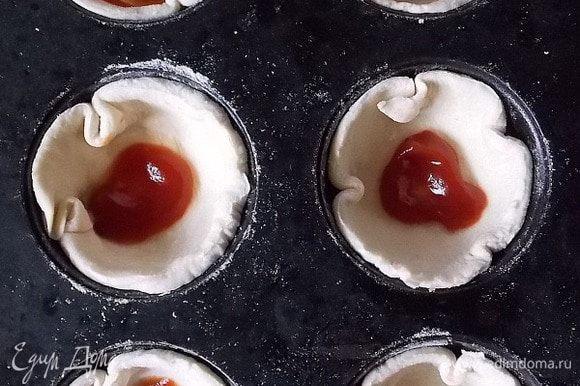 Слоеное тесто раскатать (1 лист — 250 г), не сильно, вырезать круги и кладем в смазанную маслом форму для кексов. Добавить немного кетчупа.