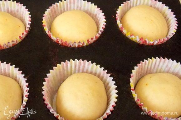 Подошедшее тесто разделить на 15–16 частей. Раскатать не очень сильно, распределить шоколадную начинку, защипать края и скатать в шарики. Разложить их в бумажные формочки для кексов. По желанию смазать верх сладким чаем.
