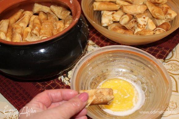Каждый блинчик окунайте в растопленное сливочное масло и складывайте в глиняный горшок.