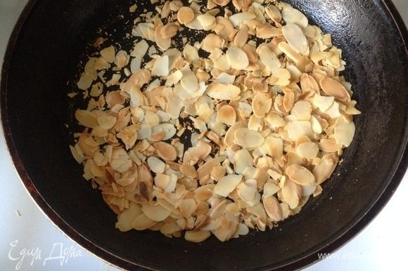 Миндальные лепестки подсушите на сковороде до золотистого цвета. И украсьте лепестками тортик.