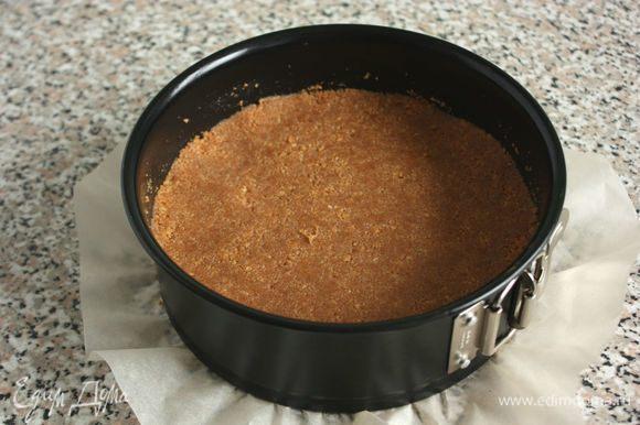 На дно разъемной формы положить бумагу для выпечки, затем надеть кольцо, бортики смазать жиром. Полученную смесь выложить в подготовленную форму и тщательно утрамбовать.