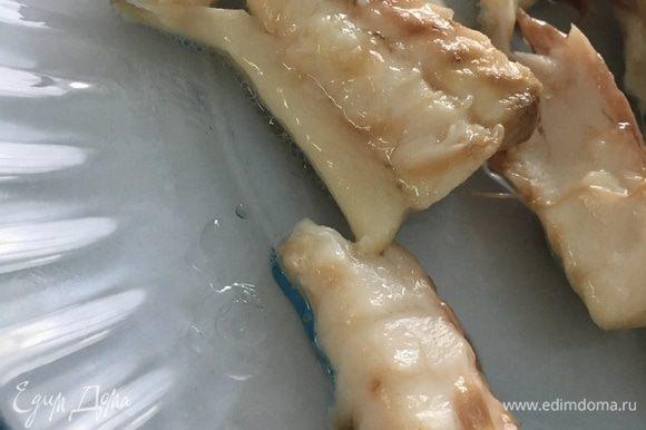Отварную рыбу отделить от костей на крупные куски.